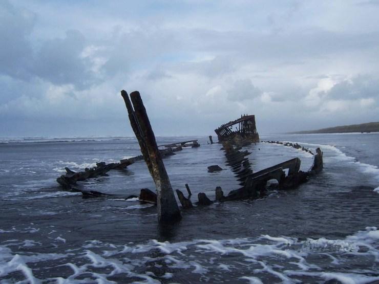 Remains of a metal sailing ship lying on an Oregon beach