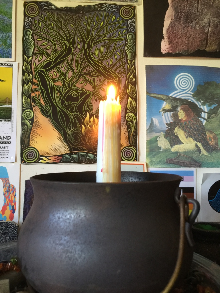 Candle burning in a cauldron, on an altar