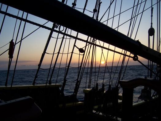 The sun setting through the rigging of a tall ship