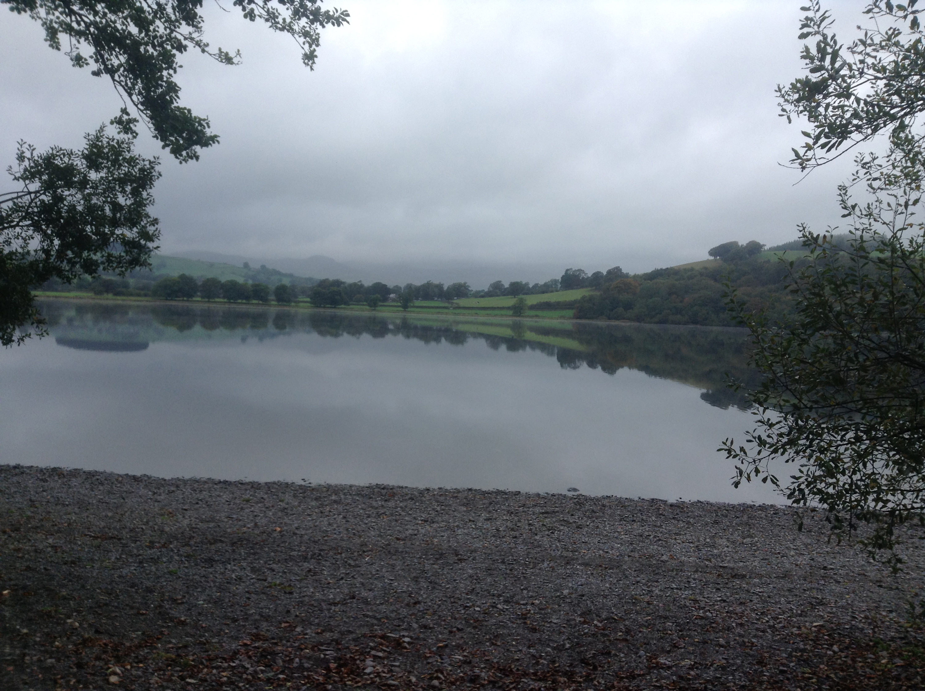 Grey sky, the green hills reflected in the still waters of the lake