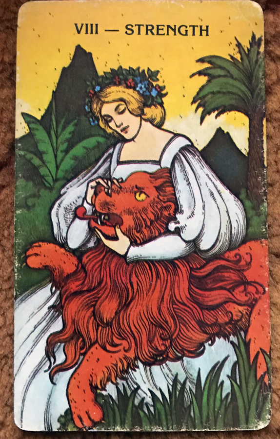 A woman in a white dress pushes a gaudy lion's mouth closed.